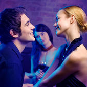 Young couple and woman looking at them at club — Stockfoto