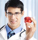 Smiling doctor with apple, at office — Stockfoto