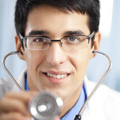 Happy doctor with stethoscope, at office — Stock Photo