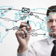 Young business man drawing a global network with envelopes on world map. — Stock Photo