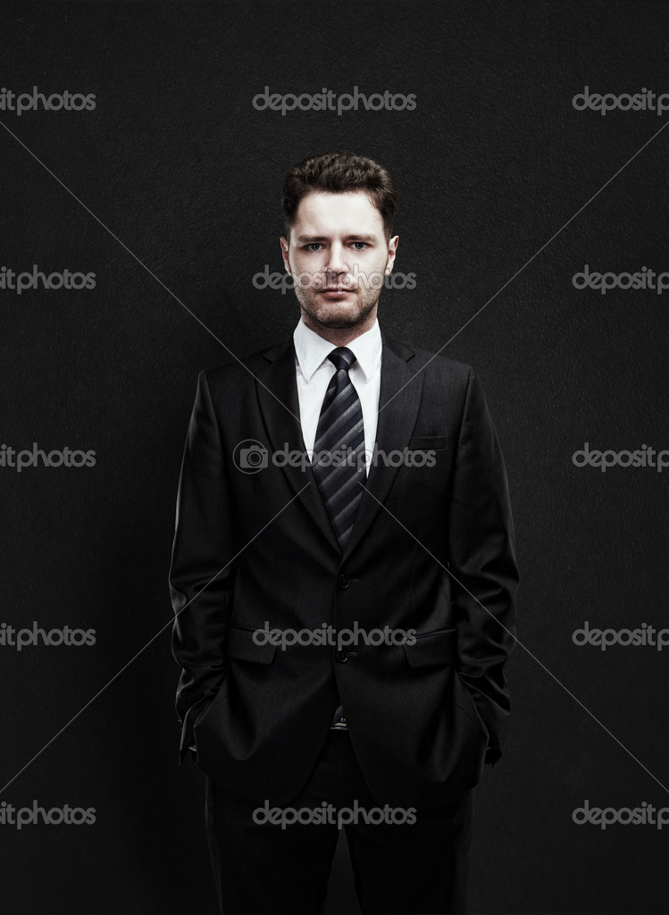 Portrait of a young businessman standing with his hands in the pockets. Young handsome man  looking confident. On a black background — Stock Photo #10105232