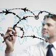 Young business man drawing an airplane routes on world map — Stock Photo
