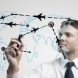 Stock Photo: Young business man drawing an airplane routes on world map