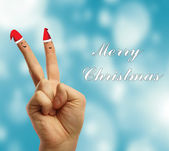Fingers dressed in Santa-Claus red-white hats. — Stock Photo
