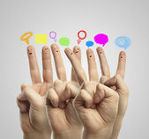 Happy group of finger smileys with social chat sign and speech bubbles — Stock Photo