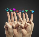 Group of happy finger smileys with love heart speech bubbles — Stock Photo