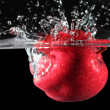 Stock Photo: Red apple dropped into water