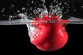 Red apple dropped into water — Stock Photo