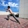 Young man doing exercises on the roof of building — Stock Photo