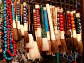 Brushes and necklaces at the chinese market — Stock Photo