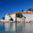 sveti stefan in the early morning sunshine and calm seas — Stock Photo