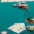 A glass of liquor and cards and dollars — Stock Photo