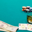 A glass of liquor and cards and dollars — Stock Photo #9974524