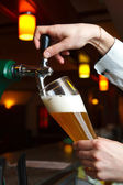 The bartender pours the beer — Stock Photo