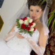 Stock Photo: Bride in a designer dress holding a rose bouquet