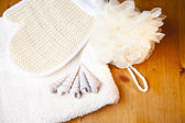 Luxury bath or shower set with towel, glove and shells on wooden background — Stock Photo