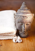 Luxury bath or shower set with towel, buddha and shells on wooden table — Stock Photo