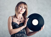 The beautiful girl holds a vinyl record — Stock fotografie