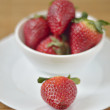 Ripe strawberry in a white saucer — Stock Photo