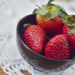 Ripe strawberry in a black saucer — Stock Photo
