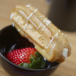 Stock Photo: Ripe strawberry on black plate with eclair and cup