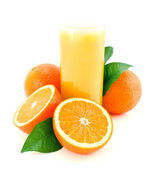 Ripe oranges with green leaves and juice glass. — Stock Photo
