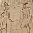 Egyptian hieroglyphic carvings on a wall - Stock Photo