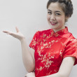 Asian Chinese woman in Traditional Chinese Cheongsam gesturing — Stock Photo #8443097