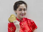 Beautiful asian woman wear cheongsam and holding golden heart — Stockfoto