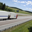 Trucking on long highway - Stock Photo