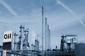 Oil refinery and commercial fuel sign — Stock Photo