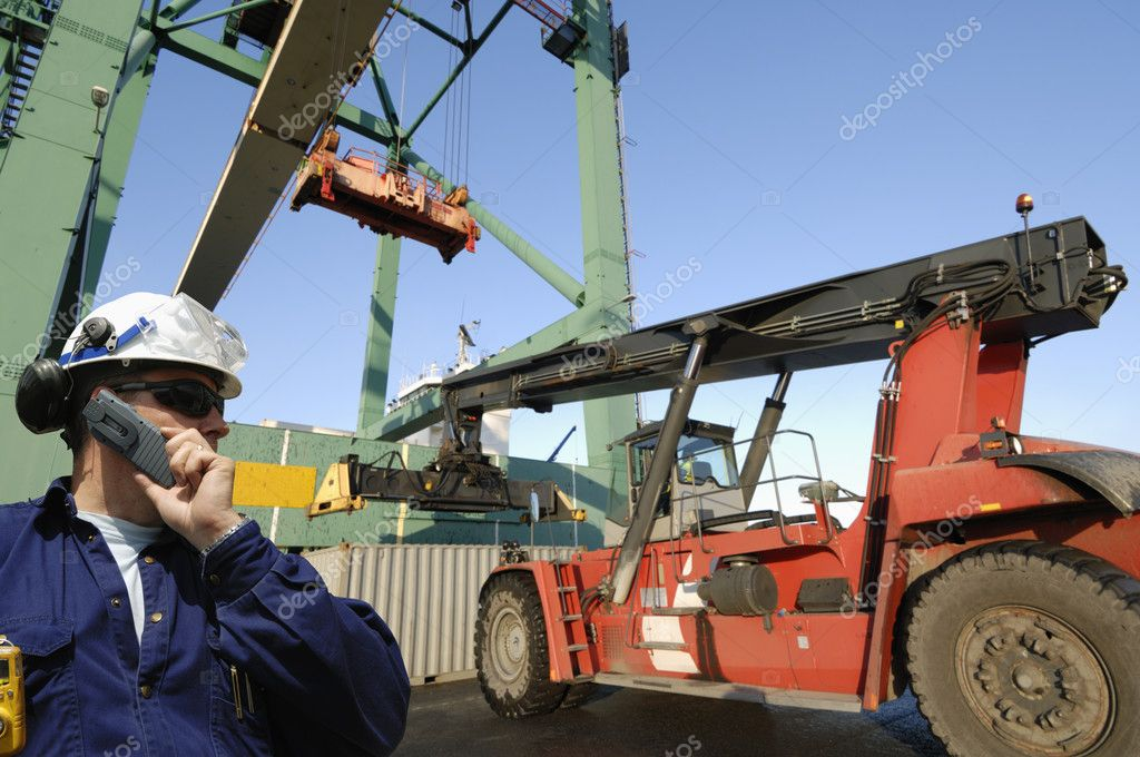 Worker, port-worker, with large forklift and container crane in background — Stock Photo #8307975