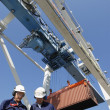 Dock workers and container crane — Stock Photo