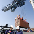 Stock Photo: Dock workers, truck and container crane