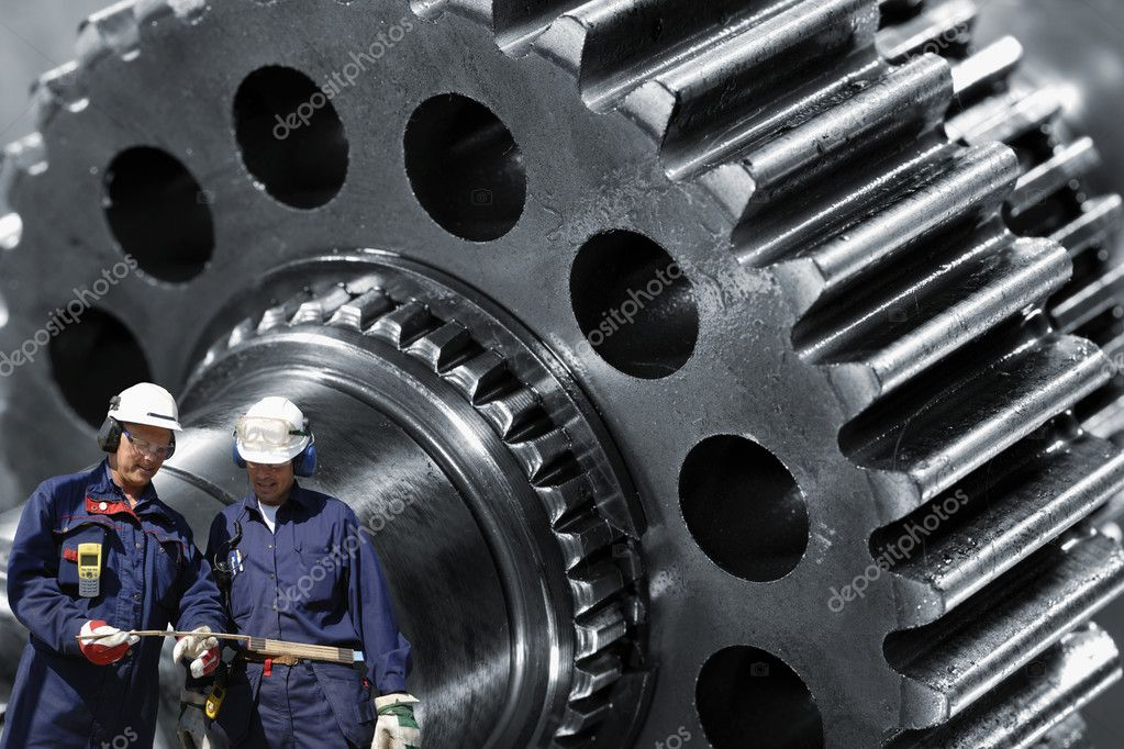 Two metal, steel-workers with large gear wheel machinery in background — Stok fotoğraf #8374522
