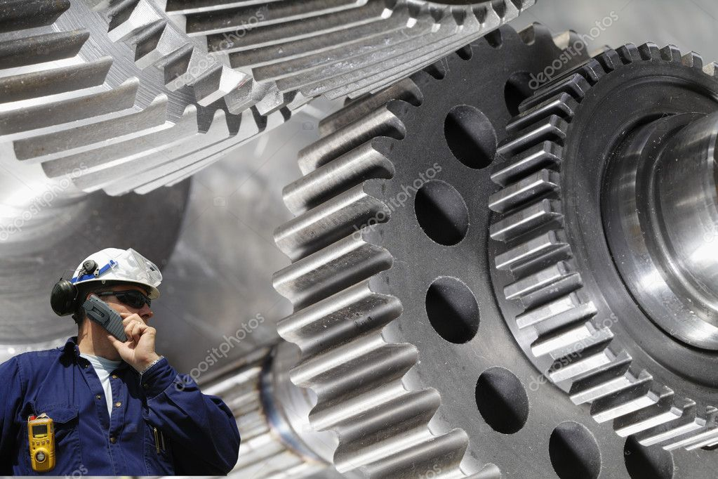 Engineer, worker, with large gear wheel machinery in background  Stock Photo #8558237