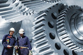 Steel-workers and giant machinery — Stock Photo