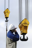 кран, крючки и строительных рабочих, выступая на своем телефоне — Стоковое фото