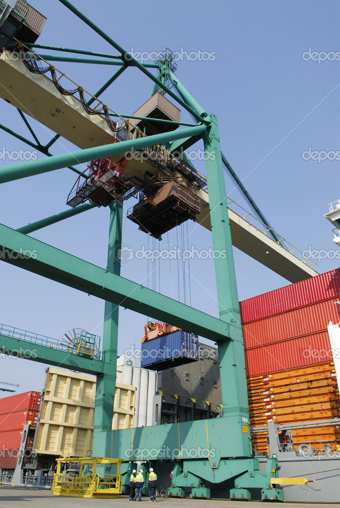 Large container-crane stacking containers on to ship, elevated view of busy commercial port  Stock Photo #8886127