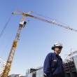 Contruction workers, cranes and machinery — Stock Photo