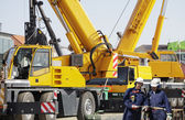 Giant mobile cranes and site-workers — Stock Photo
