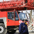Building workers and giant red mobile crane — Stock Photo #9953044