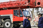 Building workers and giant red mobile crane — Stock Photo