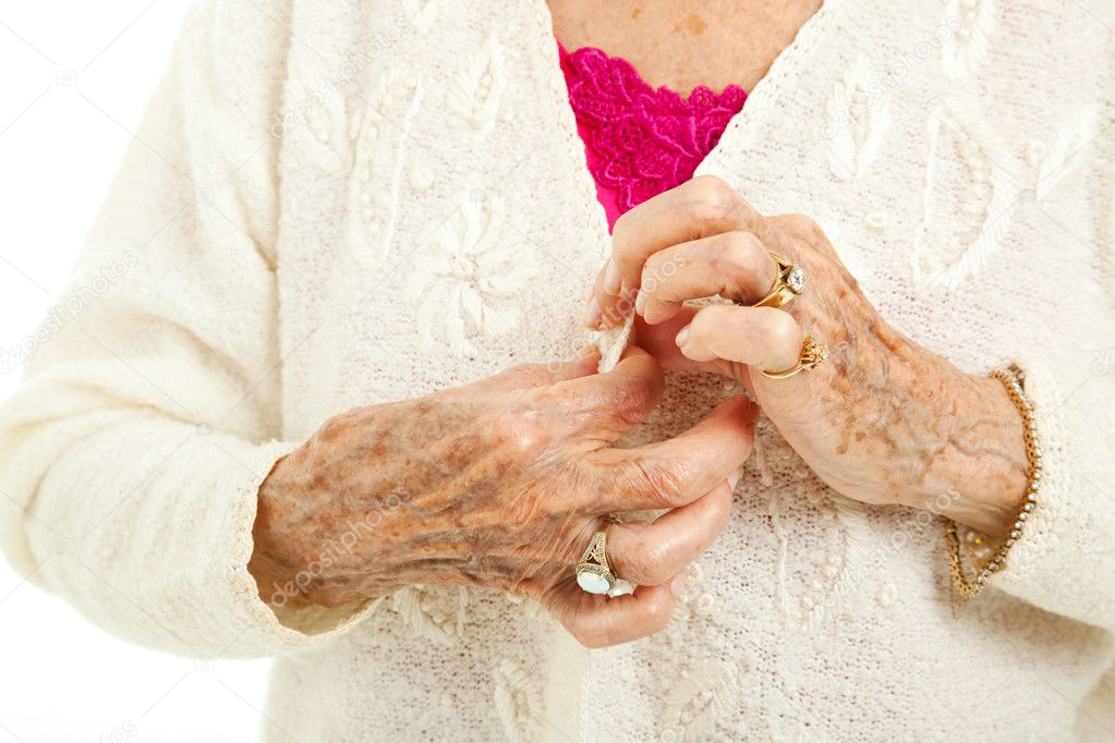 Senior woman's arthritic hands struggling to button her sweater. — Stock Photo #8592335