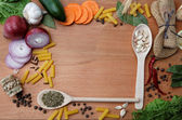 Frame made of spices and vegetables on a wooden table. — Stock Photo