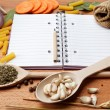 Notebook for recipes and spices on wooden table — Stockfoto #10631451