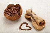 Srdce kávová zrna v lněné tkaniny. — Stock fotografie