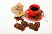 Two hearts made from coffee beans around a cup of coffee o — Stock Photo