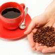 Heart in hand made ​​from coffee beans around a cup of coffe — Stock Photo