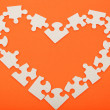 Foto de Stock  : Puzzles in shape of heart on orange background.